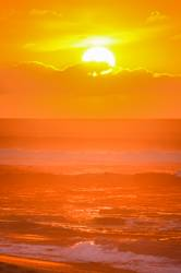 Sun setting over waves on Sunset Beach, Hawaii, USA