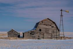 Vintage barn and windmill surrounded by snow in Canada