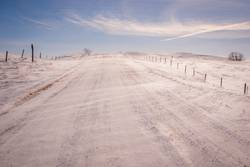 Snow blowing over gravel road in a Canada winter