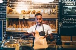 African man works in pastry shop.
