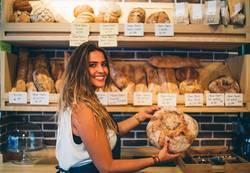 Woman sells in bakery.