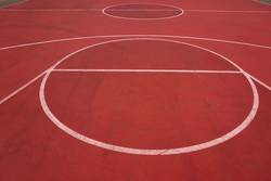 red basketball court with white lines on the street