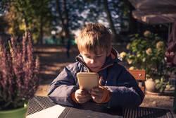 Kind mit Smartphone sitzt draussen im Herbst