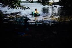kleiner Junge im Wasser mit Krokodil Luftmatratze