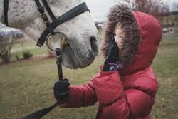 Mädchen in roter Winterjacke spricht mit ihrem Pferd