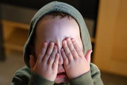 Kleiner Junge mit Kapuze hält sich die Augen zu