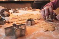 Kinderhände stechen Weihnachtsplätzchen aus