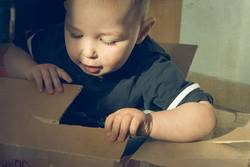 Kleiner Junge im Pappkarton
