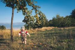 Kleiner Junge in Lederhosen rennt vor Apfelbaum
