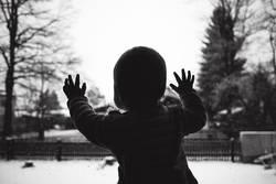 Baby schaut aus Fensterscheibe im Winter