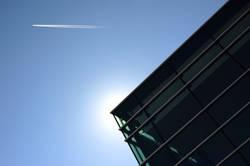 Ecke eines modernen Gebäudes mit Sonne und Flugzeug