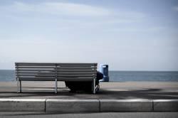 Obdachloser schläft am Strand eines Urlaubsortes