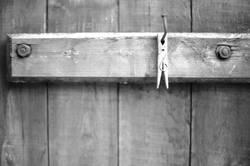 Alte Wäscheklammer an einem Nagel im Holztor