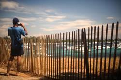 Mann fotografiert eine Bucht im Mittelmeer bei Sonnenschein