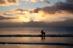 Surfer und Sohn am Strand in Mauritius im Sonnenuntergang