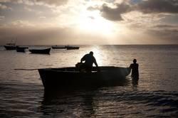 Fischerboot und Fischer im Sonnenuntergang