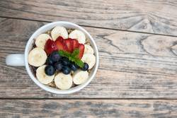 Acai bowl strawberry blueberry banana wooden table