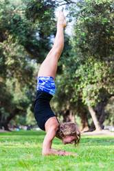 Young girl standing on her head doing yoga in the park