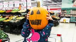 Little girl holding a pumpkin in her hands, on Halloween.