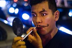 Portrait of a young clown putting on mustaches with makeup
