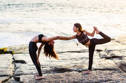 Two girls on the beach doing yoga at sunset. Lima Peru.