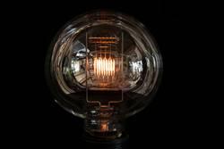 große Glühbirne mit glühendem Glühfaden und Spiegelungen