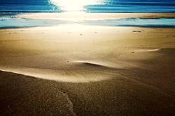 Goldsand trifft stahlblaues Wasser