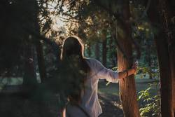 Lifestyle photo of a girl in the forest at golden hour