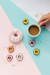 Coffee, colorful cookies, donut and sprinkles flat lay