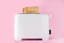 Toasted toast bread in toaster on pink background