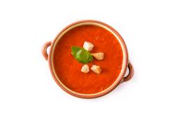 Tomato soup in brown bowl isolated on white background.