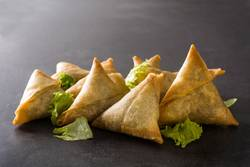 Samsa or samosas with meat and vegetables on black background.