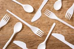 Disposable plastic cutlery on wooden table. Top view