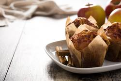 Apples and cinnamon muffins on wooden table.