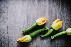 Zucchinis mit Blüten auf Steinplatte