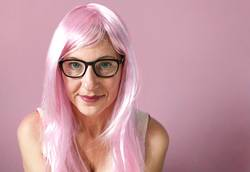 lady with pink hair smiling on pink background
