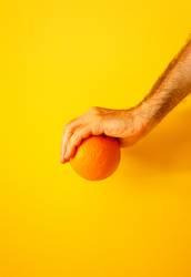 orange in hand on yellow wall II