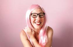 woman with pink wig smiling happily on pink background