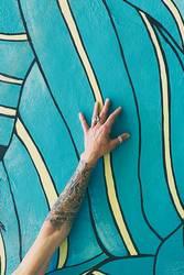 Tattooed arm on wall with graffiti