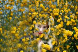 smiling young woman between yellow flowers