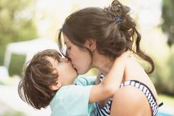 mother and son kiss in summer day
