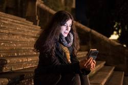 Sit woman on cathedral stairs looking smartphone