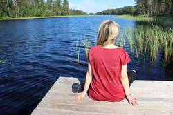 Young woman sitting near lake in Karelia, Finland