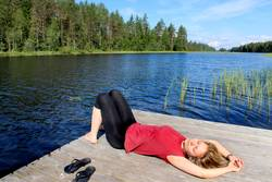 Young woman relaxing near lake in Karelia, Finland