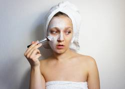 Young beautiful woman applying mask on her face