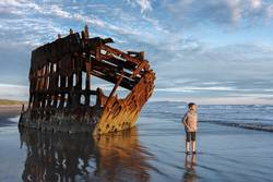 Boy stands by shipwreck in sun setting light.
