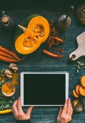 Hände mit Tabletten-PC auf Küchentisch mit Kürbis