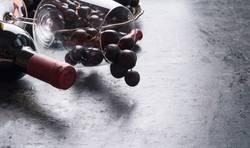Weinglas mit roten Trauben und Flasche Rotwein
