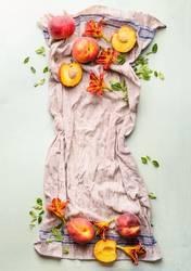 Ganze und halbe Pfirsiche auf Küchentuch mit Blättern