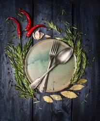 Löffel und Gabel auf dem Teller mit Gewürzen umrahmt